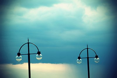 Two street lamps on evening sky